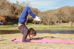 做在湖的岸的妇女瑜伽 库存图片