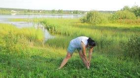 做在湖的深色的妇女伸展运动早晨 影视素材