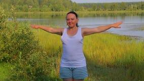做在湖的深色的妇女伸展运动早晨 股票录像