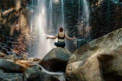 做在瀑布前面的妇女瑜伽姿势 免版税图库摄影