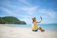 做在热带海滩的美丽的亚裔妇女selfie 库存图片