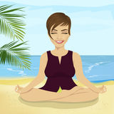 做在热带海滩的年轻微笑的女实业家瑜伽 免版税库存图片
