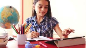 做在片剂个人计算机的十几岁的女孩家庭作业 股票录像