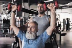 做在现代健身房的严肃的老运动员锻炼与教练员 库存图片
