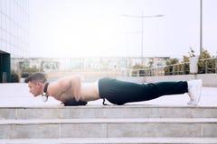 做在现代体育中心前面的年轻男性俯卧撑 S 免版税库存照片
