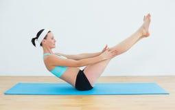 做在瑜伽席子的适合的妇女小船姿势 免版税库存图片