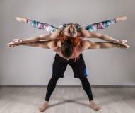 做在瑜伽assanes的人和少妇力量锻炼 Acroyoga概念 免版税库存图片