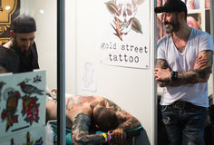 做在男性客户的专业艺术家纹身花刺后边 库存图片
