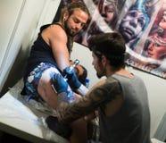 做在男性客户腿的艺术家五颜六色的纹身花刺 库存图片