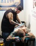 做在男性腿的专业艺术家五颜六色的纹身花刺 图库摄影