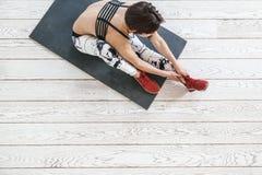 做在白色地板的妇女适合的锻炼 库存图片