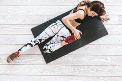 做在白色地板的妇女适合的锻炼 免版税图库摄影