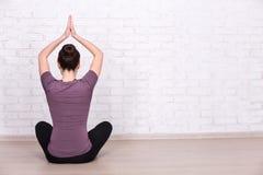 做在白色砖墙的后面观点的亭亭玉立的运动的妇女瑜伽 库存图片