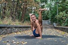 做在的英俊的微笑的灵活的运动人瑜伽asanas 免版税库存照片