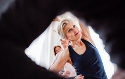做在社区活动中心俱乐部的小组资深人民锻炼 库存照片