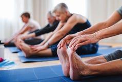 做在社区活动中心俱乐部的小组资深人民锻炼 库存图片