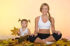 做在秋天的妇女和孩子瑜伽 库存照片