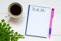 做在笔记本写的名单 与要做在木书桌上的名单的笔记本有咖啡的 免版税图库摄影