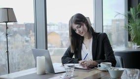 做在笔记本的俏丽的妇女笔记 坐在咖啡馆的年轻女实业家在木桌上 在桌上是灰色的 股票录像