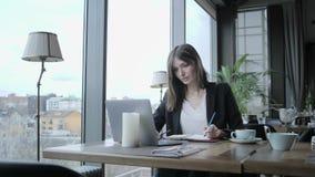 做在笔记本的俏丽的妇女笔记 坐在咖啡馆的年轻女实业家在木桌上 在桌上是灰色的 股票视频