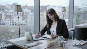 做在笔记本的俏丽的妇女笔记 坐在咖啡馆的年轻女实业家在木桌上 在桌上是灰色的 影视素材