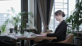 做在笔记本的妇女的特写镜头手笔记 坐在咖啡馆的年轻女实业家在木桌上 股票录像