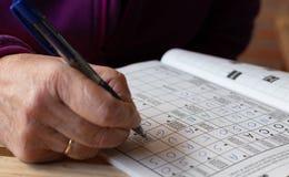 做在笔记本的资深人的手纵横填字游戏的 休闲和时间 免版税库存照片