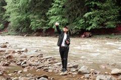 做在粗砺的河背景的人selfie  库存照片