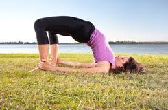 做在绿草的美丽的少妇瑜伽锻炼 免版税库存图片