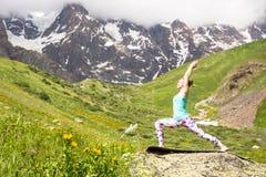 做在美丽的山的少妇瑜伽 好的视图 库存照片