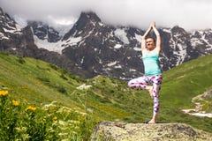 做在美丽的山的少妇瑜伽 好的视图 免版税库存图片