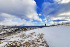 做在美丽的积雪的岩石的旅行摄影师图片在一个晴天 海岛lofoten 美丽的域前景横向挪威草莓 库存照片