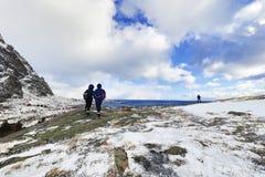 做在美丽的积雪的岩石的旅行摄影师图片在一个晴天 海岛lofoten 美丽的域前景横向挪威草莓 库存图片