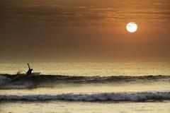 做在美好的日落的冲浪者一个完善的轮在北秘鲁 免版税图库摄影