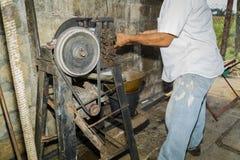 做在老葡萄酒机械齿轮后的古巴工作者糖蔗汁 免版税库存图片