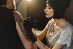 做在肩膀的少妇文身的人纹身花刺 免版税图库摄影