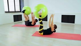 做在腹肌的男人和妇女锻炼使用fitball 影视素材