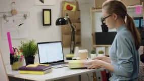 做在膝上型计算机的少女家庭作业用在桌上的咖啡 股票视频