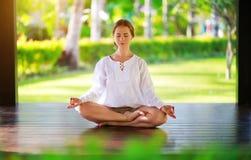 做在自然的年轻女人瑜伽在公园 免版税库存图片