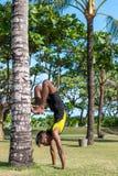 做在自然的年轻瑜伽人实习者瑜伽 草的亚裔印地安信奉瑜伽者人在公园 巴厘岛 图库摄影