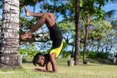 做在自然的年轻瑜伽人实习者瑜伽 草的亚裔印地安信奉瑜伽者人在公园 巴厘岛 库存照片