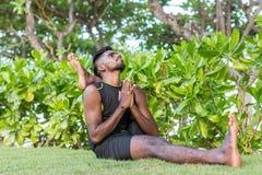 做在自然的年轻瑜伽人实习者瑜伽 草的亚裔印地安信奉瑜伽者人在公园 巴厘岛 库存图片