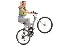 做在自行车的少妇一个自行车前轮离地平衡特技 免版税库存照片