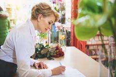 做在花店的快乐的妇女笔记 库存图片
