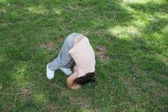 做在草坪的女孩翻筋斗 图库摄影