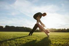 做在草坪的年轻夫妇杂技瑜伽 库存图片