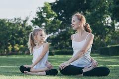 做在草的母亲和女儿瑜伽锻炼在公园在 免版税库存图片