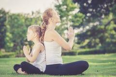 做在草的母亲和女儿瑜伽锻炼在公园 库存照片