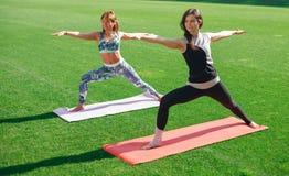 做在草的运动服的两个少妇瑜伽在体育场 库存照片