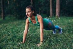 做在草的适合的少妇俯卧撑锻炼在森林里 免版税库存图片